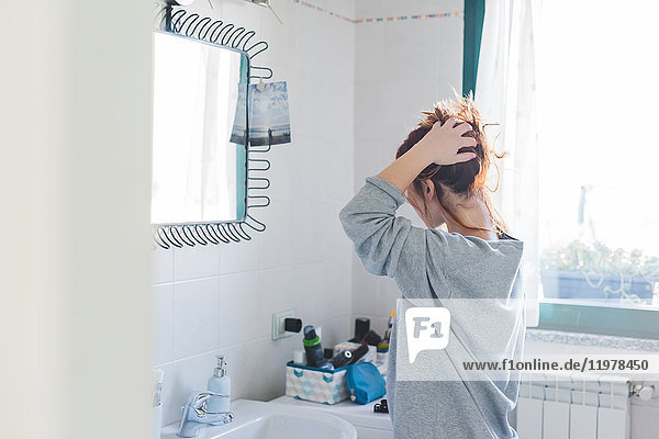 Young woman styling hair up at bathroom mirror
