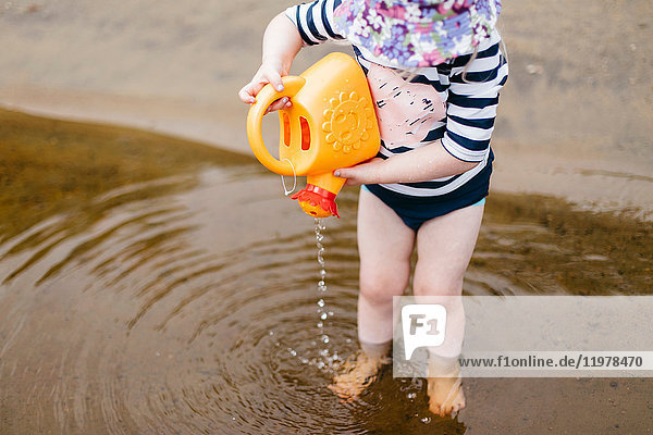 Girl standing ankle deep in lake pouring water from toy watering can  Huntsville  Canada