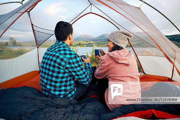Couple sitting in tent  drinking hot drinks  looking at view