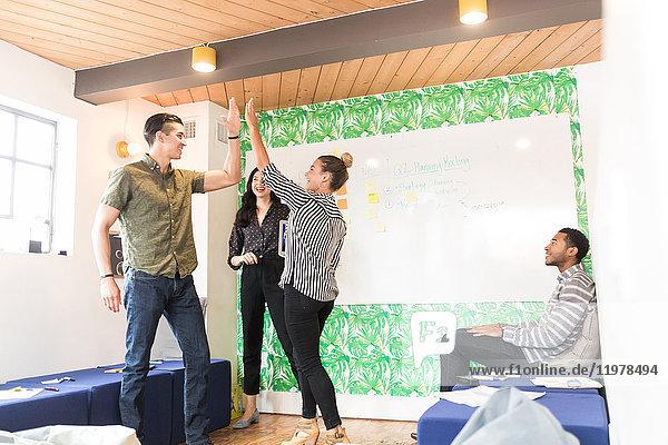Junge Geschäftsmänner und -frauen geben sich im kreativen Sitzungssaal die Klinke in die Hand