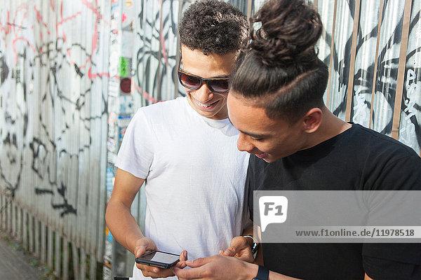 Zwei junge Bösewichte auf der Straße  die ein Smartphone anschauen