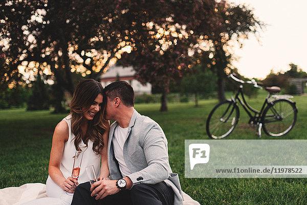 Romantisches junges Paar mit rosa Champagner flüstert in der Abenddämmerung im Park