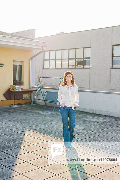 Portrait of young woman strolling on roof terrace with hands in pockets