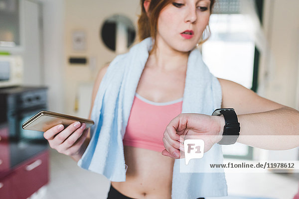 Young woman training,  looking at smartwatch