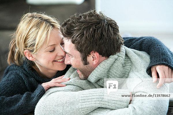 Glückliches Paar in Rollkragenpullovern  die sich gegenseitig anstarren