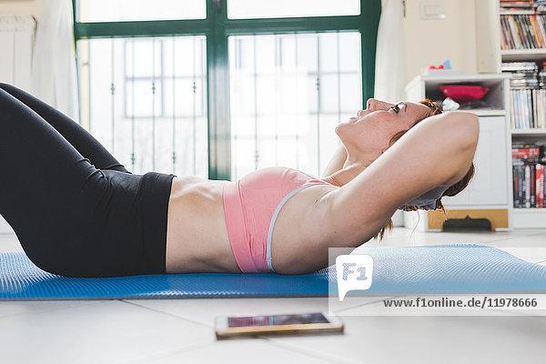 Young woman doing sit ups on yoga mat
