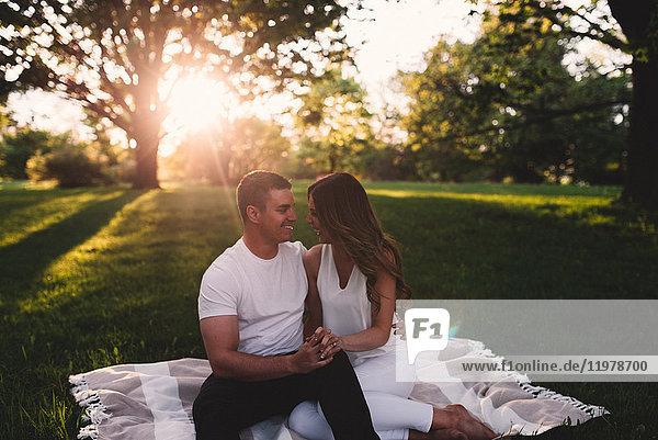 Romantisches junges Paar sitzt im Park und hält sich bei Sonnenuntergang an den Händen
