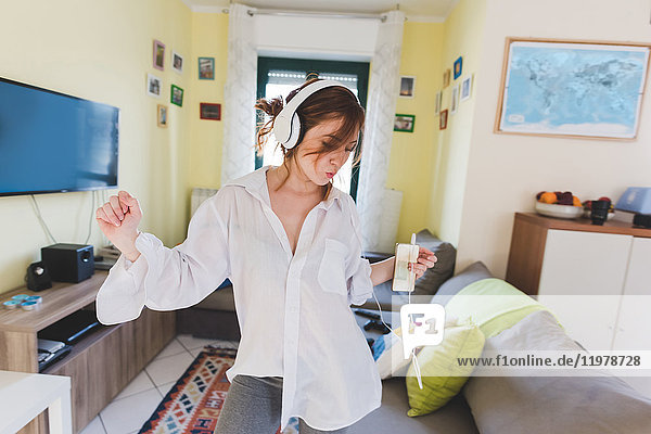 Young woman in sitting room dancing to smartphone music on headphones