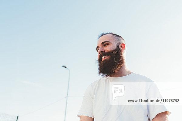Porträt eines bärtigen Mannes  der lächelnd wegschaut