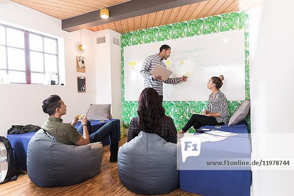 Junger Geschäftsmann zeigt auf Whiteboard in kreativem Besprechungsraum