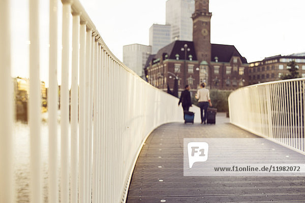 Businesswomen with suitcases on footbridge Businesswomen with suitcases on footbridge