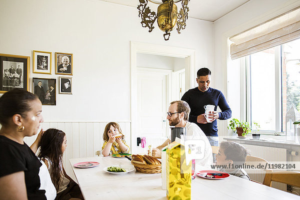 Adults and children (2-3  6-7) in dining room