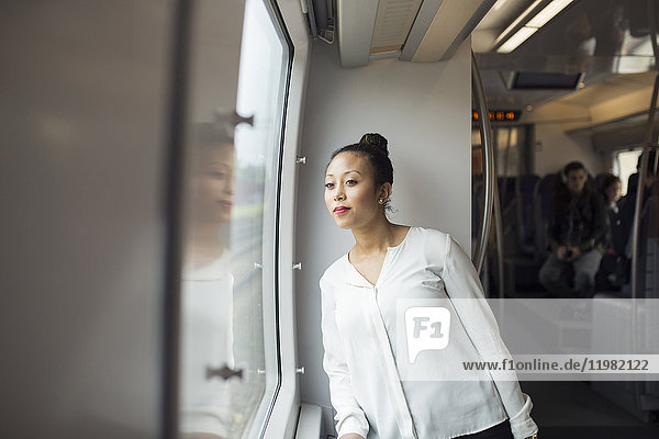 Woman looking through window in train