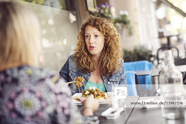 Woman eating pasta while sitting at table with friend