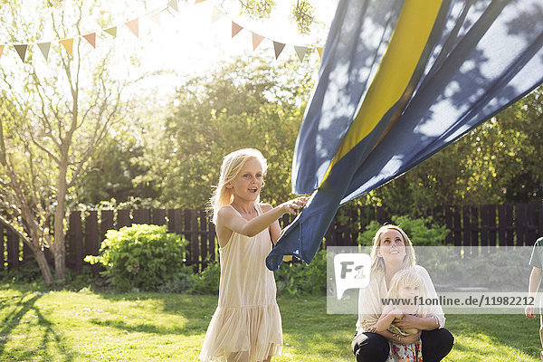 Mother with child (18-23 months) watching her daughter (8-9) holding Swedish flag
