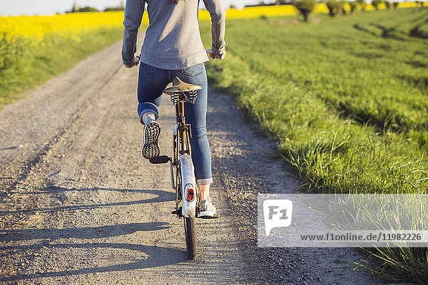 Rear view of woman cycling on country road