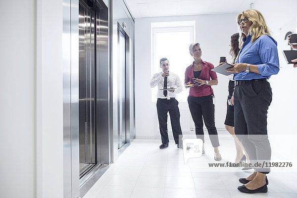 Architects and project managers waiting for elevator