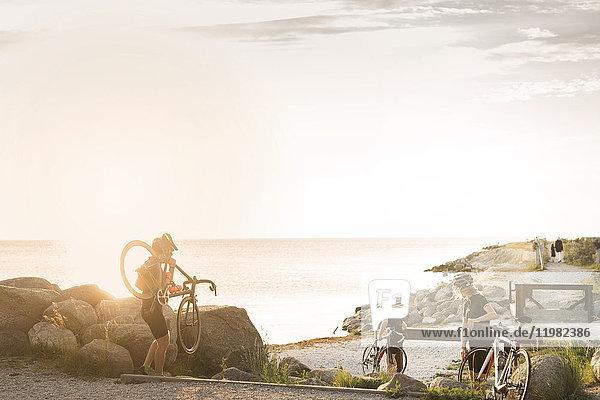 Three cyclists by sea Three cyclists by sea