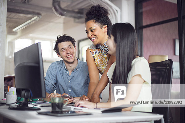 Coworkers smiling in front of computer monitor