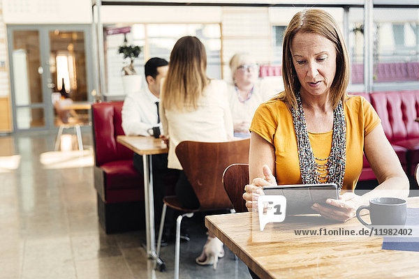 Woman using digital tablet in cafeteria