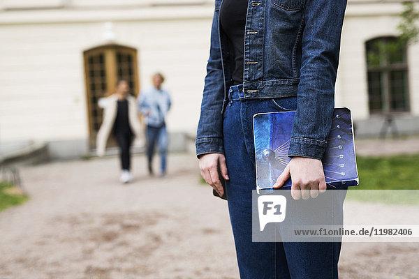 Student standing in schoolyard  holding book