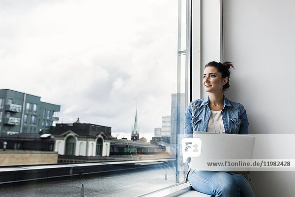 Young woman with laptop looking through window
