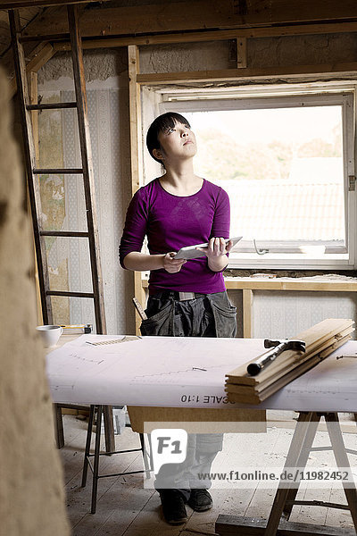 Woman working on renovating old attic with tablet