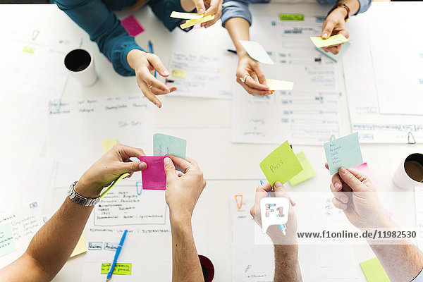 Colleagues using adhesive notes during business meeting