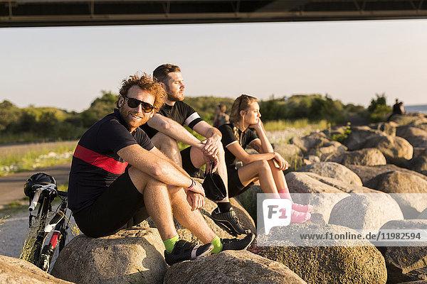 Three cyclists by bridge Three cyclists by bridge