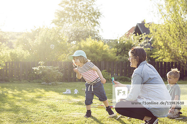 Woman and children (2-3  4-5) blowing bubbles in garden