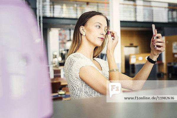 Young woman correcting make-up at table