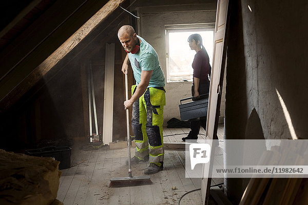 Couple working on renovating old attic
