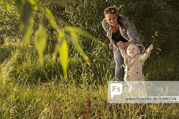 Mother with son (18-23 months) standing by tree