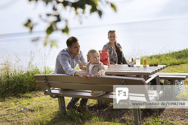Parents with son (18-23 months) sitting by picnic table
