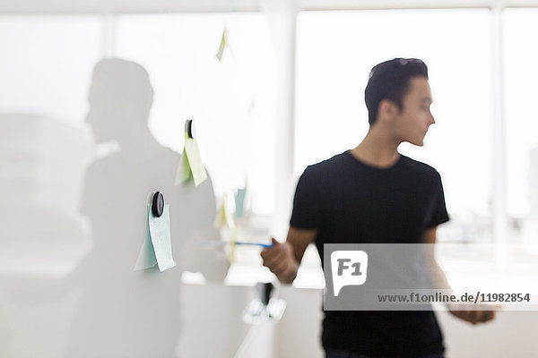 Young businessman standing next to whiteboard