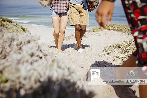 Beine eines multiethnischen Paares auf einem sonnigen Sandstrandweg im Sommer