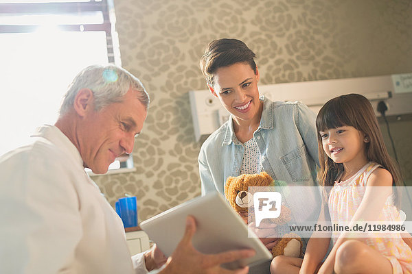 Male doctor showing digital tablet to girl patient and mother in hospital room