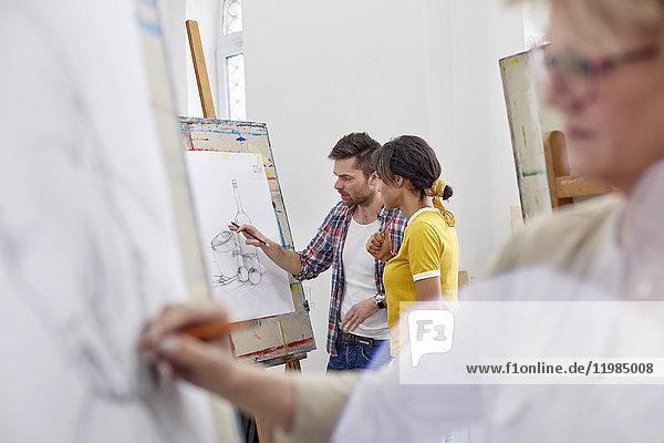 Künstler diskutieren Skizze an der Staffelei im Atelier der Kunstklasse