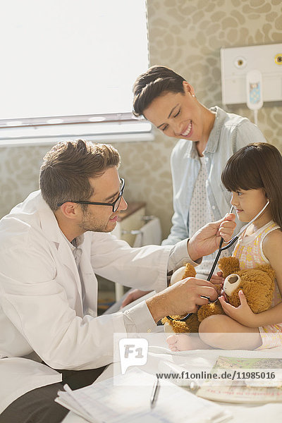 Male doctor showing stethoscope to girl patient in hospital room