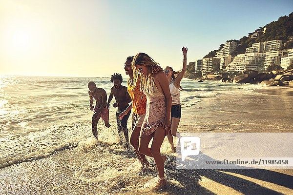 Verspielte junge Freunde beim Spaziergang im sonnigen Sommer auf dem Meer