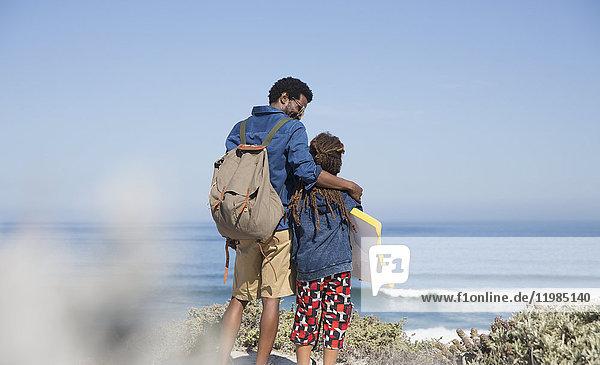 Vater und Sohn wandern mit Boogie-Board am sonnigen Sommerstrand des Ozeans