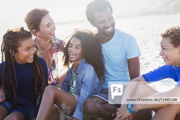 Multiethnische Familie lacht am sonnigen Sommerstrand
