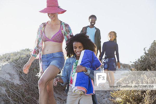 Lächelnder Familienspaziergang auf dem sonnigen Strandberg im Sommer