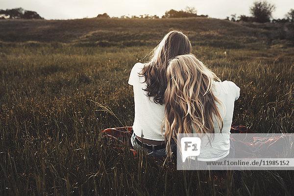 Ruhige Teenager-Schwestern in weißen T-Shirts im ländlichen Raum