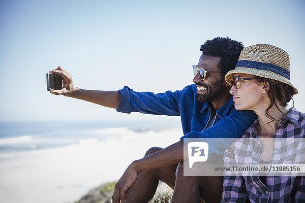 Ein multiethnisches Paar  das sich an einem sonnigen Sommerstrand niederlässt.