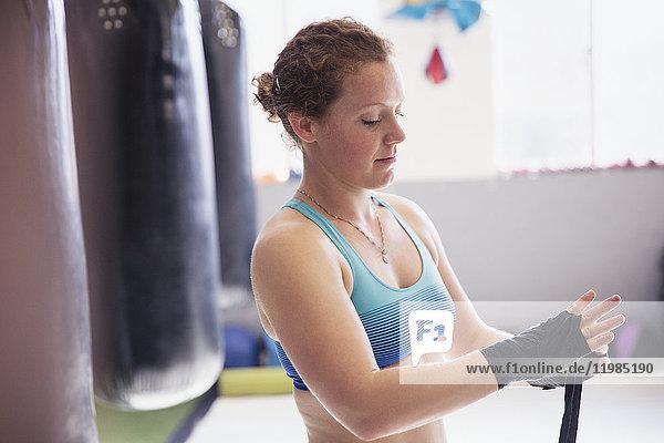 Boxerinnen wickeln Handgelenke neben Boxsack im Fitnessstudio ein