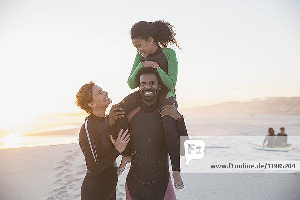 Portrait verspielte Familien-Surfer in Neoprenanzügen am Sommer-Sonnenuntergangsstrand