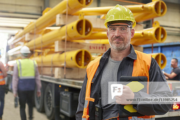 Portrait confident male engineer with digital tablet in factory