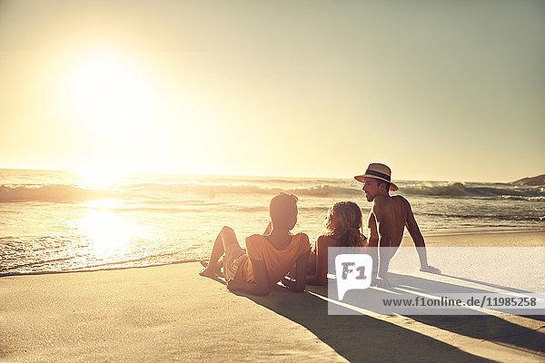 Junge Freunde entspannen sich am idyllischen  sonnigen Sommer-Sonnenuntergang am Meeresstrand.