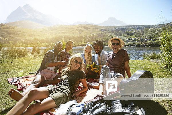 Portrait lächelnde junge Freunde beim Picknick am sonnigen Sommerufer des Flusses